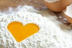 Ovo da gema no conceito do cozimento do amor da farinha Fotografia de Stock