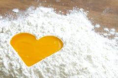 Ovo da gema no conceito do cozimento do amor da farinha Fotografia de Stock Royalty Free