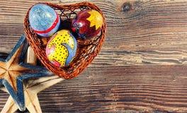 Ovo da páscoa colorido em uma cesta do coração e em uma estrela do mar seca foto de stock