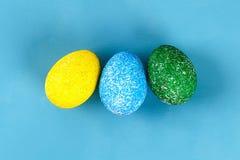 Ovo da páscoa de Diy pintado com arroz colorido em um fundo azul A decoração dos ovos para a Páscoa foto de stock royalty free