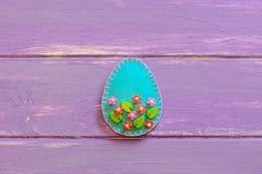 Ovo da páscoa de feltro no fundo de madeira roxo com lugar vazio para o texto Ofícios do ovo de feltro com flores plásticas foto de stock royalty free