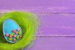 Ovo da páscoa de feltro no ninho no fundo de madeira roxo com espaço vazio para o texto Cartão de Páscoa bonito da mola Easter fe imagens de stock
