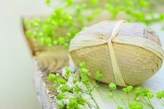 Ovo da páscoa decorativo Handcrafted envolvido em flores amarelas pequenas da mola do papel do ofício no estilo de madeira resist Foto de Stock Royalty Free