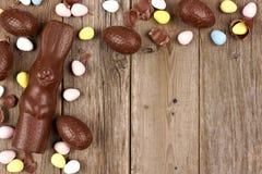 Ovo da páscoa do chocolate e beira de canto do coelho contra a madeira rústica Fotos de Stock Royalty Free