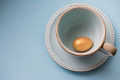 Ovo da páscoa do ouro em uma caneca da porcelana em um fundo azul Vista superior Copie o espa?o fotos de stock