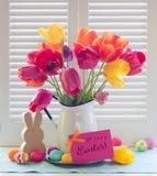Ovo da páscoa e Tulip Bouquet Still Life coloridos na luz da janela com o cartão de Páscoa Hoppy foto de stock
