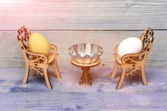 Ovo da páscoa em cadeiras de madeira na tabela com bacia metálica Fotos de Stock