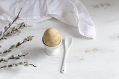 Ovo da páscoa naturalmente tingido para o café da manhã, copo de ovo branco, guardanapo drapejado, tabela de madeira branca, banc foto de stock royalty free