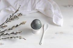 Ovo da páscoa naturalmente tingido para o café da manhã, copo de ovo branco, guardanapo drapejado, tabela de madeira branca, banc fotografia de stock