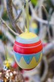 Ovo da páscoa pintado à mão que pendura em uma árvore branca com fundo do bokeh foto de stock royalty free