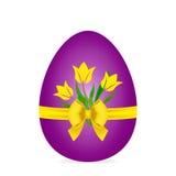 Ovo da páscoa, roxo com tulipas, curva e a fita amarelas Imagem de Stock