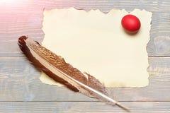 Ovo da páscoa vermelho com pena da escrita e papel na madeira Imagem de Stock Royalty Free