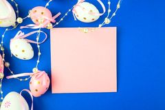 Ovo da p?scoa decorado com p?rolas em um fundo azul e em uma folha de papel cor-de-rosa fotografia de stock royalty free