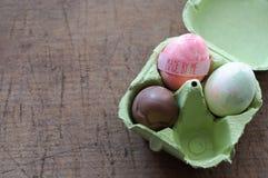 Ovo de chocolate e ovo pintado à mão no pacote de ovo Fotografia de Stock Royalty Free