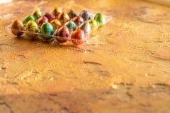 Ovo de codorniz no ninho, mola, isolada no amarelo Canto de uma bandeja de ovos coloridos Conceito feliz de Easter Foco seletivo imagem de stock royalty free