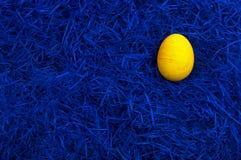 Ovo de easter amarelo na obscuridade - azul imagem de stock royalty free