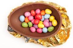 Ovo de Easter do chocolate meio na folha Fotografia de Stock