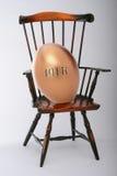 ovo de ninho 401K na cadeira de madeira Imagens de Stock Royalty Free