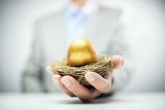 Ovo de ninho dourado das economias da aposentadoria na mão do homem de negócios imagem de stock