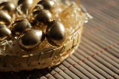 Ovo dourado em cestas de vime, fundo da Páscoa foto de stock royalty free