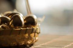 Ovo dourado em cestas de vime, fundo da Páscoa imagens de stock