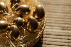 Ovo dourado em cestas de vime, fundo da Páscoa fotografia de stock royalty free