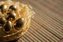 Ovo dourado em cestas de vime, fundo da Páscoa imagem de stock royalty free