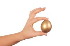 Ovo dourado na mão Fotos de Stock Royalty Free