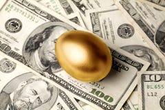 Ovo e dólares dourados Fotos de Stock Royalty Free