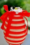 Ovo em listras vermelhas e brancas com uma fita vermelha e uma flor pequena imagens de stock royalty free