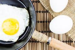 Ovo frito em uma frigideira e em dois ovos crus em uma tabela de madeira Fotos de Stock Royalty Free