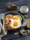 Ovo frito, feijões no molho de tomate com cebolas e cenouras, pepinos frescos e tomates, pão de centeio caseiro - café da manhã d Imagem de Stock