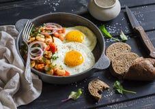 Ovo frito, feijões no molho de tomate com cebolas e cenouras, pepinos frescos e tomates, pão de centeio caseiro - café da manhã d Foto de Stock Royalty Free