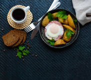 Ovo frito no salame e em batatas cozidas Submissão de uma frigideira com um pão da xícara de café e de centeio Pequeno almoço imagens de stock