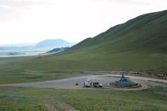 Ovoo nelle montagne della Mongolia sul passaggio Automobile con un rimorchio, un motociclista e una carrozza ferroviaria vicino fotografia stock