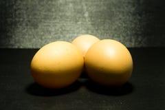 Ovos amarelos no fundo preto do teste padrão Fotos de Stock