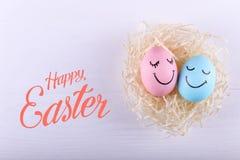 Ovos azuis e cor-de-rosa com sorrisos pintados no ninho, espaço da cópia Projeto de cartão feliz do conceito da Páscoa imagens de stock royalty free