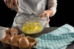 Ovos batendo da mulher com um batedor de ovos em uma bacia Fotografia de Stock Royalty Free