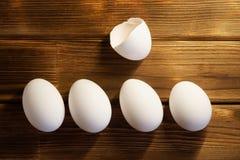 Ovos brancos da galinha em uma tabela de madeira Inteiro e quebrado naughty fotos de stock
