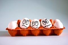 Ovos brancos da galinha engraçada com caras em uma pilha de ovo foto de stock