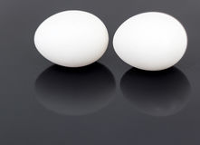 Ovos brancos da galinha isolados no fundo lustroso preto Foto de Stock