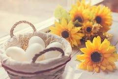 Ovos brancos e flores amarelas Fotos de Stock