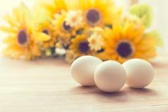 Ovos brancos e flores amarelas Fotografia de Stock Royalty Free