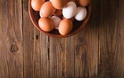 Ovos brancos e marrons em uma bacia cerâmica em um fundo de madeira Estilo rústico Ovos Conceito da foto da Páscoa Imagem de Stock Royalty Free
