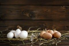 Ovos brancos e marrons na palha e no fundo escuro de madeira fotografia de stock