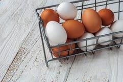 Ovos brancos e marrons no fim da cesta do metal acima Fotografia de Stock