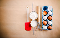 Ovos brancos e marrons, suiça e copos com farinha e açúcar Imagens de Stock Royalty Free