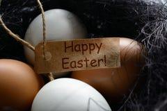 Ovos brancos e marrons um ninho do sisal com a Páscoa feliz da etiqueta do cumprimento Foto de Stock