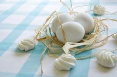 Ovos brancos e merengue da Páscoa em uma toalha de mesa azul Fotos de Stock Royalty Free
