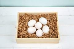 Ovos brancos em um fundo de madeira Imagens de Stock